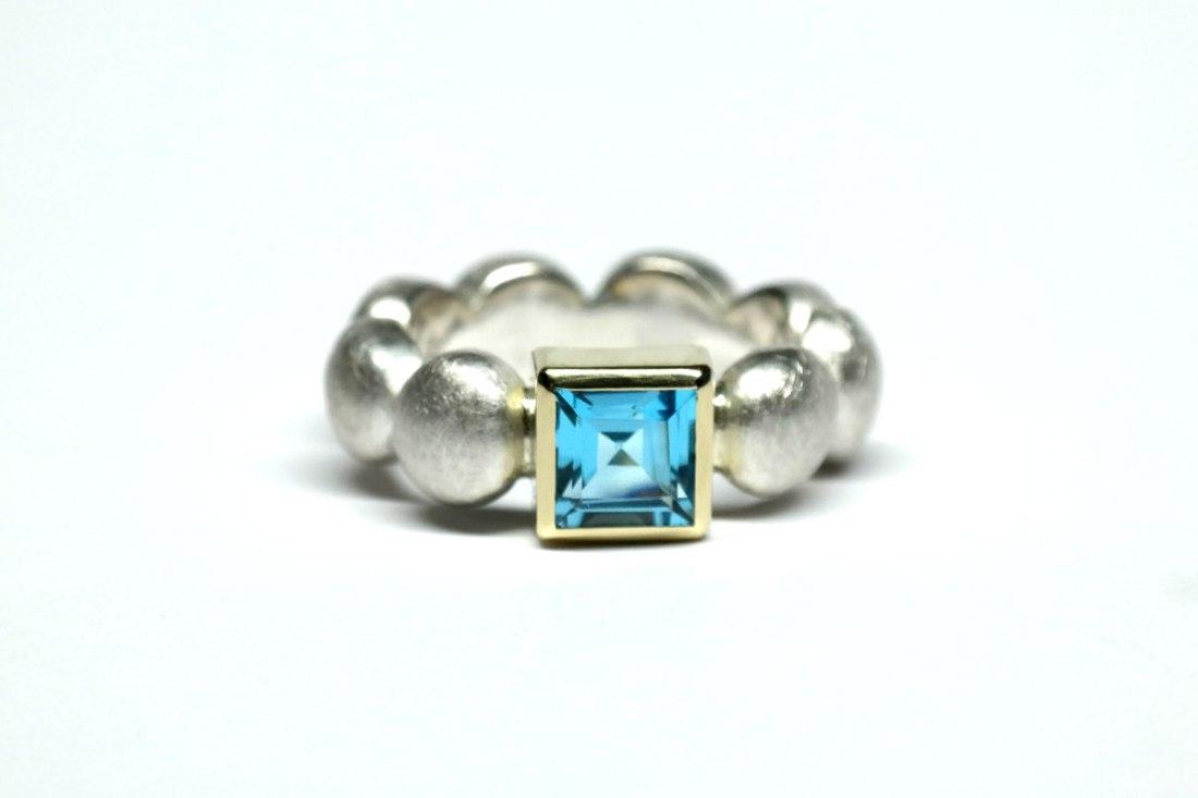Silberring-mit-blauem-Edeltopas-in-Goldfassung