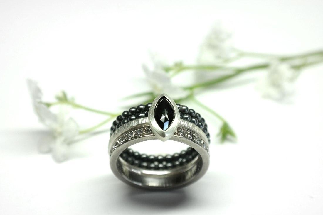 Silbersteckring-mit-schwarzem-Diamant-und-Blume-im-Hintergrund